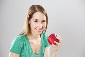 usmievajuca sa zena s jablkom v ruke